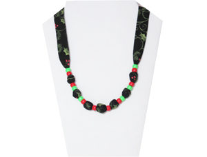 Christmas necklace with black cotton ties and green and red pony beads.