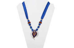 Indigo blue necklace on silky fabric with glass leaf pendant in blues and reds