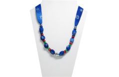 A Christmas necklace on blue snowflake cotton fabric with red, green and silver pony beads