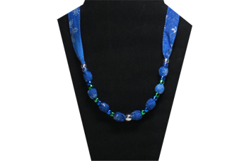 A Christmas necklace with silver snowflake pattern on indigo blue cotton fabric with pony beads