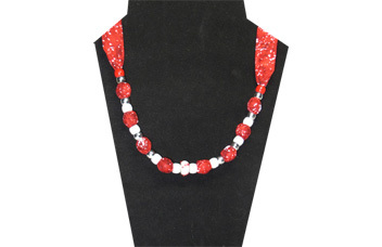 A Christmas necklace with red cotton fabric and red and white beads