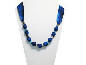 A Christmas necklace in dark blue cotton fabric with gold star and silver tone beads