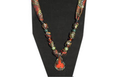 A dark paisley fabric with tear shaped glass pendant with burnt orange flower