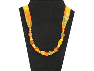 Bright orange and yellow cotton necklace with pony beads and center glass bead