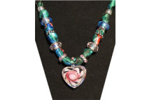 Green silky fabric necklace with small glass heart with rose painted on it.