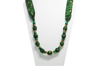 A Christmas necklace with gold pattern on a dark green cotton fabric with pony beads