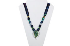A multi-color blue, red, purple silky necklace with leaf shaped glass pendant