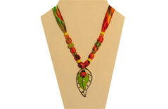 A bright necklace in multi-colored fabric with a metal pendant of a ladybug on a leaf
