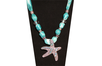 A summery necklace in soft light teal tones with metal pendant of starfish with rhinestones inset
