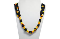A fall/autumn/Halloween necklace with orange, yellow and black candy corn on black background with pony beads