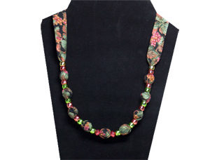 An elegantly rich looking simple necklace with green and rose pony beads with grapes and leaves on black cotton fabric.