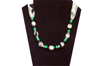 A fun necklace with printed US currency on green and white fabric