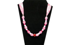 Pink fabric with pink and white beads with red glass beads in center.