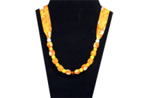 This is a very bright necklace with white, yellow and orange beads and a faceted amber bead in the center. The fabric is brightly colored with orange, yellow and white flowers in cotton.