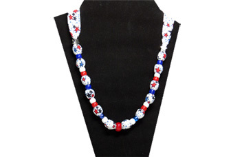 This patriotic necklace has lots of red and blue stars on white cotton fabric. The necklace has a red glass bead in the center, two silver tone metal stars and red white and blue pony beads.