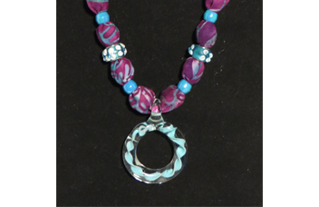 Closeup of purple necklace with round glass pendant