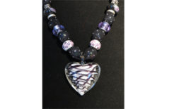 Necklace with black fabric and white, purple and black glass heart pendant