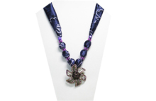 A vintage looking necklace elegantly displaying a metal pendant in the shape of a flower with purple rhinestones