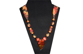 This necklace has a leaf pendant with red and gold glass. The fabric is cotton with leaves of red, gold and orange. The beads are wooden, and black gold tone and orange pony.
