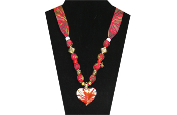 This necklace has a pretty red and white glass heart pendant. The beads are gold tone metal and it has a gold tone flower charm. The fabric is a cotton multi-colored red with purple olive leaf pattern.