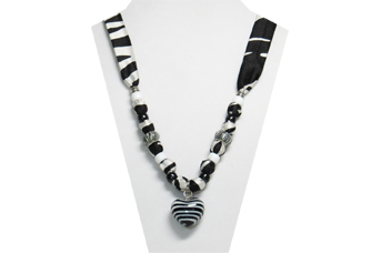This necklace has a glass black and white zebra looking heart pendant that goes nicely with the silky black and white zebra patterned fabric. The beads on the ties have a set of glass black and white striped, white pony beads and silver tone metal beads.