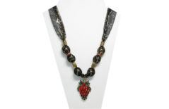 This necklace has a gold metal pendant with red glass rhinestones on a black sheer gold web design fabric. The beads are gold tone metal and red rhinestones.