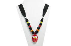 The necklace has a red glass owl pendant with white eyes and yellow beak. The fabric is black cotton with tiny gray flowers. The beads are yellow, white, red glass and yellow glass with raised red dots.