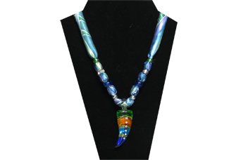 This necklace has a multi-colors dagger-like glass pendant of deep blue, turquoise, gold and green colors with clear rhinestones inset in the center. The fabric is silky green, blue and purple leaf pattern. The beads are silver tone, dark blue glass and clear rhinestone.