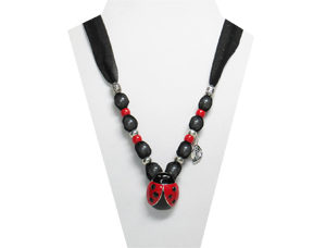 The necklace has a red and black metal ladybug pendant. The fabric is sheer black with sparkles. The beads are silver tone, red pony, and has a silver ton leaf charm.
