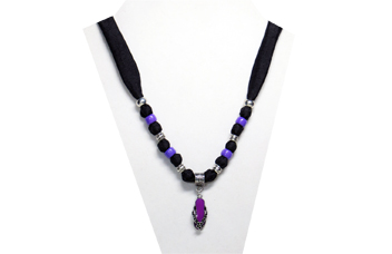 This necklace has a small purple flip-flop pendant with silver tone metal strap and flower. The fabric is black silky with beads of silver tone and purple pony beads.
