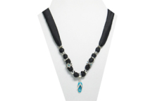 This necklace has a small silver tone metal flip-flop with a turquoise sole and clear rhinestones on the strap and sole. The fabric is black silky with beads that are silver tone metal, and silver tone metal flower with turquoise rhinestones.