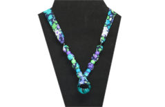 This fun and cheerful looking necklace has a variegated turquoise colored ring pendant. The fabric is black cotton with purple, turquoise, green and white floral design. The beads are are black, purple, green and turquoise ponies.