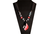 A sparkly black sheer fabric with a bright contemporary designed glass pendent of a red, black and silver pattern. The beads are red glass, clear rhinestone on silver tone metal and plain silver tone metal.