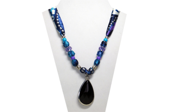 This necklace's pendant is a black faceted teardrop rimed in silver tone metal. The silky fabric is multi-color blue, turquoise, purple and silver. The beads are purple faceted and silver tone metal.
