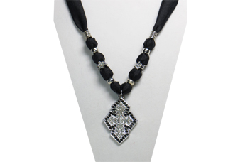 An elegantly designed necklace with black silky fabric and a sparkly black and clear metal rhinestone cross pendant. The beads are of designed silver tone metal.