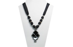 A dressy necklace with black silky fabric and a cross pendant of black flat onyx-like stone and clear rhinestone edging. The beads are silver tone metal including some with pretty amber rhinestones.