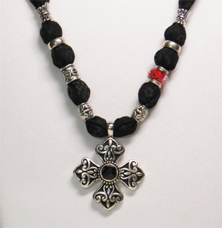 This necklace has cotton fabric with a black background and tiny gray flowers.   The cross pendant is black and silver tone metal with a black faceted piece in the center.  The beads are silver tone metal and the whole black and silver look is accented with one red glass bead with pretty designed colors throughout.