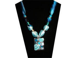 A stunning necklace with variegated turquoise cotton fabric and an oblong pendant with light and dark turquoise raised design on silver tone metal. The beads are silver tone and one with tiny flower and blue rhinestone center.