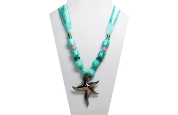 This necklace has a sea foam green silky fabric with a starfish metal pendant of silver tone metal with various green rhinestones embedded in it. The beads are teal green faceted and pony beads and pretty opaque glass beads painted pink and white.