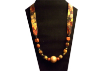 This necklace has a large round light wooden bead in the center and smaller red square beads on the ties. The fabric is cotton with a fall color leaf pattern.