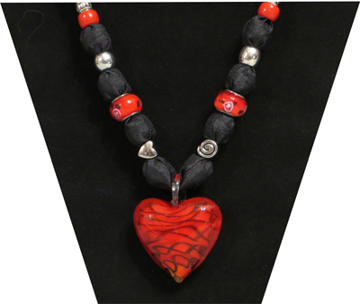 Red glass pendant with black looking ribbon running through.  The fabric is black and silky.  The beads are red glass with pink design, silver tone heart and circle design.