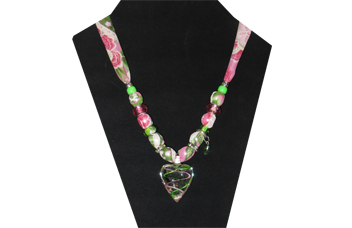 This dainty necklace has a clear glass heart pendant with pink and green lines criss-crossing through it. The fabric has a pink, white and green paisley pattern and is silky. The accent beads are green glass with painted pattern, pink faceted, delicate green rhinestone, and silver tone metal. There is a delicate green faceted charm hanging too.