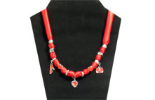 This necklace has red silky fabric with red beads and silver charms (hearts, shoe and purse). Other silver tone beads on the necklace and red rhinestone in silver tone metal.