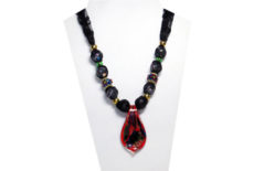 This rich looking necklace has red, blue, black and green colors on a spoon shaped glass pendant. The black lace fabric has accent beads of gold, green and blue glass with raised red yellow and green flowers.