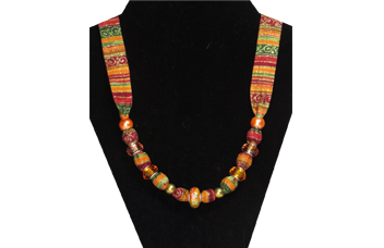 This necklace has multi-colored fabric of sparkly stripes red, orange, green and gold. There is an oriental looking bead in the center, accented with gold and peach faceted beads and pearl-like peach beads.