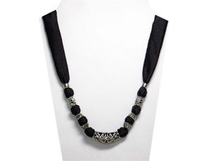 This simple but elegant necklace is a black and silver metal tube with a wrought iron design. The silky black fabric has accents of silver tone metal beads.