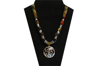 This necklace has a black and silver medallion. The silky olive colored fabric has red and black design throughout. There is a black and silver tube on each side with accent beads of silver tone metal.
