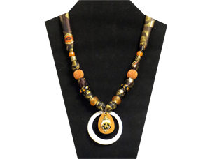 This 4-part pendent has an outer ring of white shell, brown wood middle ring with gold tone leaf and dove charms. The fabric is silky multi-colored green, black and orange on a geometric pattern. The beads are black glass with brown dots, glass-like gold, orange globe-shaped and brass tone.