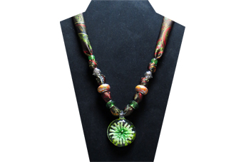 This necklace had a round clear glass pendant with white and green starburst flower inside. The silky fabric is a green, red and black paisley pattern with accents of orange cloisonne-like beads, green faceted and silver tone metal beads.