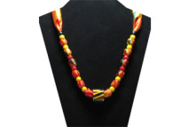 This brightly colored necklace has a clear large barber pole glass bead with stripes of yellow, blue and red inside it. The fabric is silky yellow, orange, red and green with red and yellow pony beads.